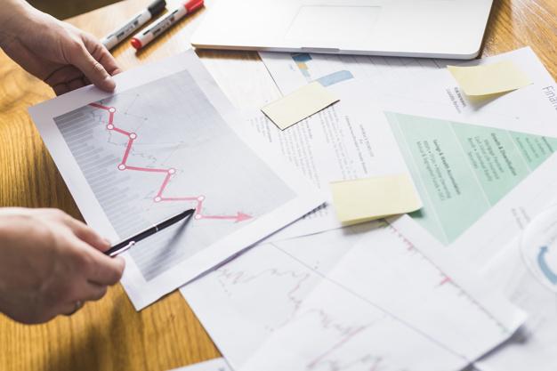 businessperson s hand analyzing increasing graph 23 2147838592 - كيف يساهم استثمار القطاعات في تحقيق رؤية قطر الوطنية 2030 ؟