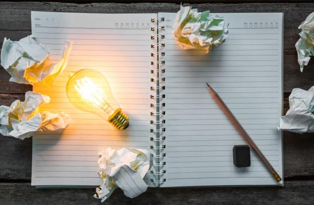 top view of lit light bulb on a notebook 1232 673 - بعض الأخطاء يجب تجنبها عند إعداد دراسة جدوى بأبوظبي